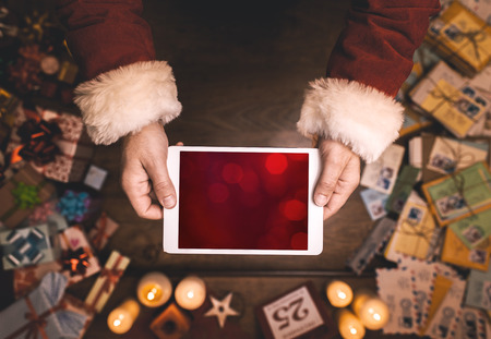 Santa Claus using a digital touch screen tablet, hands close up, top view, desktop with letters and Christmas gifts on background Stock Photo