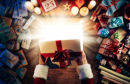 Santa Claus opening a magic bright Christmas gift box, presents and letters all around, hands top view