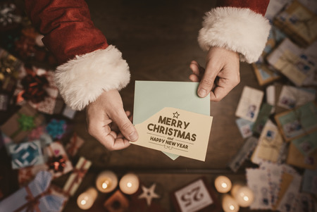 Santa claus opening an envelope and holding a Christmas card, hands close up, top view, desktop with gifts and letters on background
