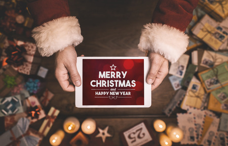 Le Père Noël en utilisant une tablette numérique à écran tactile avec Joyeux Noël et Bonne Année message, mains close up Banque d'images