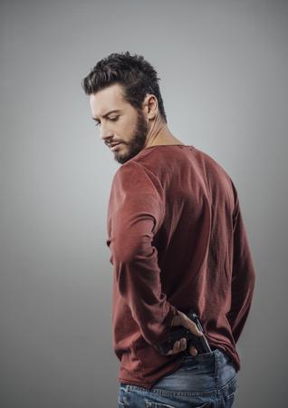 Confident aggressive man holding a gun, cool attitude Stok Fotoğraf