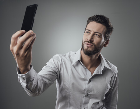 cool man: Cool handsome man taking self portraits with his smartphone Stock Photo