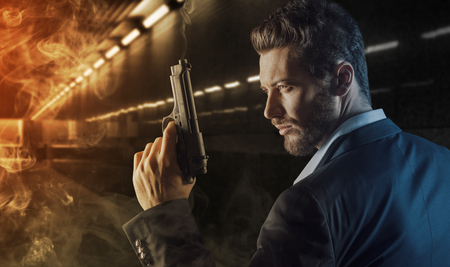 Brave handsome hero agent holding a gun and walking into the fire in an underground tunnel, danger and crime concept Banco de Imagens