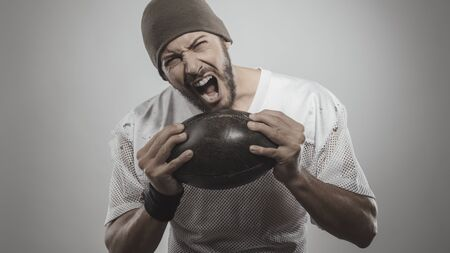 strong toughness: Handsome muscular football player holding ball and posing