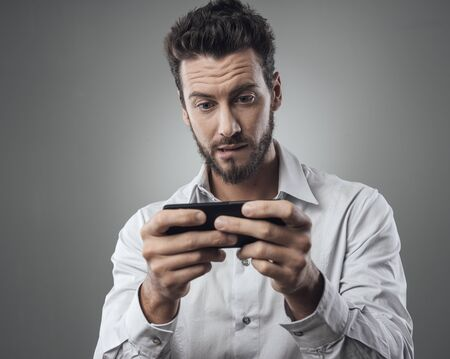 raised eyebrows: Handsome young man playing with his smartphone