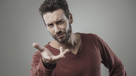 Young man frowning and gesturing with hand on gray background