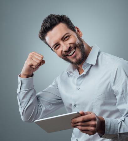 Fröhlich lächelnde Mann erhalten eine gute Nachricht auf Tablette mit erhobener Faust