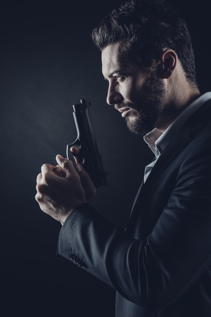 man holding gun: Brave cool man holding a gun on dark background Stock Photo