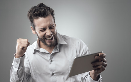 cheerful: Cheerful smiling man receiving good news on tablet with fist raised