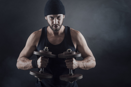 Cool confident man with cap lifting weights and working out photo
