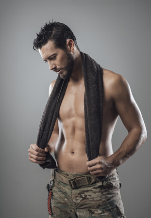 Confident muscular man drying his athletic body with a towel photo