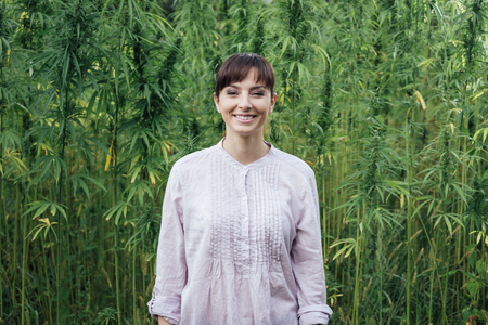 new age: Smiling woman wearing a white new age shirt and posing in a hemp field Stock Photo