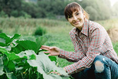 Lächelnder weiblicher Gärtner posiert mit Zucchini Pflanzen und Blick in die Kamera, Landwirtschaft und Gartenarbeit-Konzept
