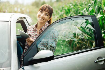 navegacion: Mujer alegre sonriente con su coche que conecta con una tableta digital, de navegación para automóviles y wi-fi concepto de conexión
