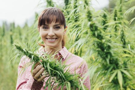 hanf: Junge lächelnde Frau in einem Hanffeld Überprüfung Pflanzen und Blumen, Landwirtschaft und Natur-Konzept