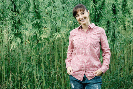 Happy young woman in a hemp field posing and smiling at camera Stockfoto