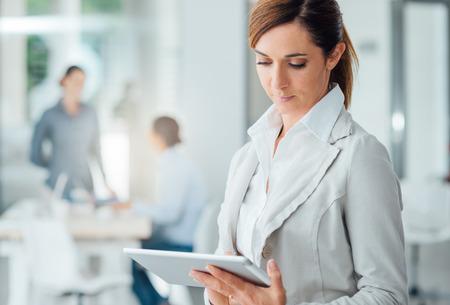 자신감 전문 비즈니스 여자 사무실에 서 디지털 터치 스크린 태블릿을 사용하여