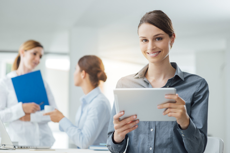 ejecutiva en oficina: Sonriente mujer de negocios usando una tableta digital y mujeres trabajadores de oficina hablando en el fondo
