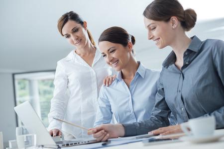 笑顔ビジネス女性チームのオフィスの机で働いて、ラップトップ上のプロジェクトを論議します。