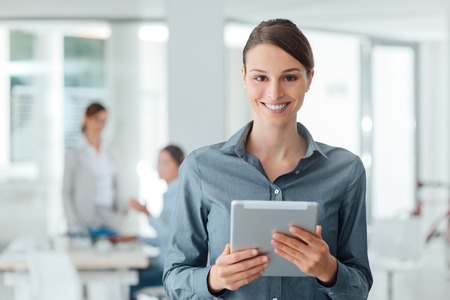 Confident smiling business woman standing in the office and using a digital tablet, business people working on background