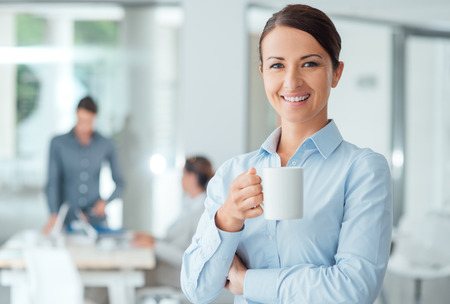 Happy confident business woman having a coffee break and holding a mug, office workers on background