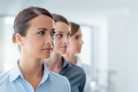 liderazgo empresarial: mujeres de negocios ambiciosos posando y mirando a otro lado, el liderazgo y las mujeres concepto de empoderamiento