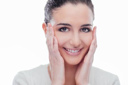 Modelo de mujer hermosa que toca su suave piel radiante rostro y sonriendo a la cámara