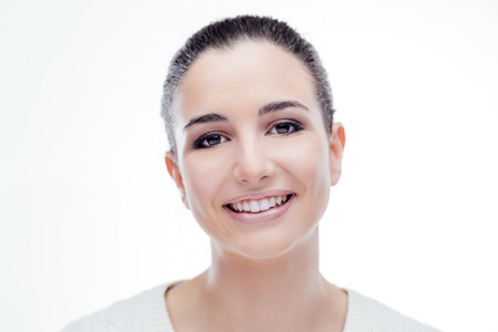 frontal portrait: Smiling attractive woman with radiant fresh face skin posing on white background