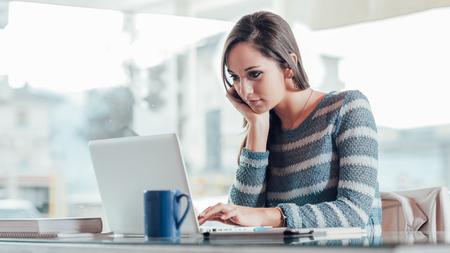 Mujer joven ocupada que trabaja con su computadora portátil en un escritorio