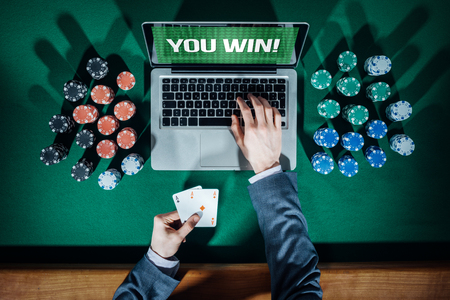 casinos: Online players hands with laptop and stack of chips all around on green table top view, he is typing and holding two aces