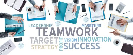Business text concepts and business team working at office desk during a meeting, hands top view, unrecognizable people, strategy and teamwork concept Stock Photo