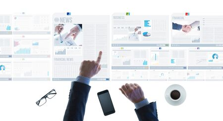 touch screen: Professional businessman pointing at financial reports and scrolling news slides on a touch screen light desk, hands close up Stock Photo