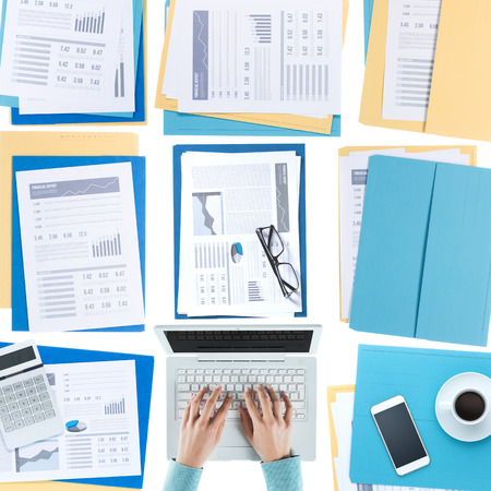 documents: Business woman working at desktop on a laptop with financial reports, paperwork and files, top view, unrecognizable person Stock Photo