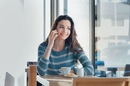 mujer bonita: Muchacha sonriente sentado en la mesa de bar y tener una llamada con su teléfono inteligente