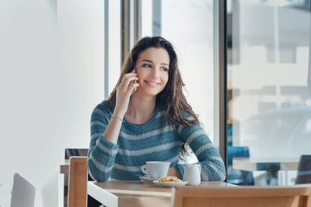 sitting pretty: Smiling girl sitting at bar table and having a call with her smart phone