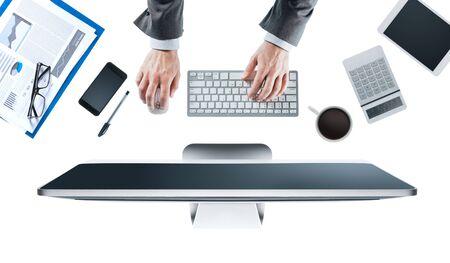 fondo blanco: Ejecutivo de negocios que trabaja en su computadora en el escritorio de oficina, fondo blanco, las manos vista desde arriba