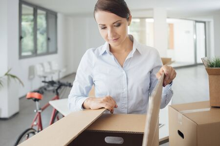 moving box: Happy confident woman unpacking and moving into her new office, she is opening a cardboard box and looking into it