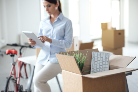 Business woman moving in a new office, she is using a digital tablet, selective focus, open cardboard box on foreground Stockfoto