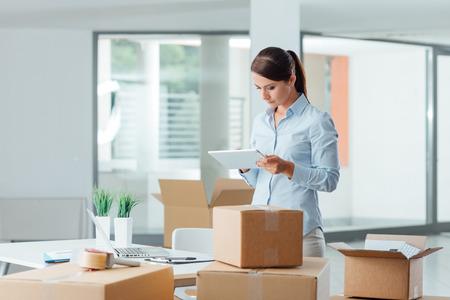 Mujer de negocios de confianza que se mueve en su nueva oficina y el uso de una tableta digital, que está rodeado de cajas de cartón