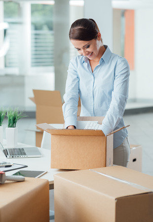 Smiling business woman unpacking a cardboard box in her new office on her desk, new job and relocation concept