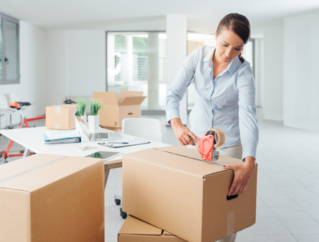 packing tape: Young business woman taping up a cardboard box in the office, relocation and new business concept