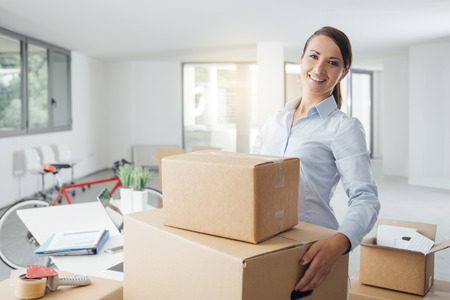 Smiling business woman carrying cardboard boxes into her new office, she is smiling at camera