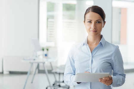 Beautiful business woman standing in the office and using a digital touch screen tablet, she is smiling at camera, room interior on background
