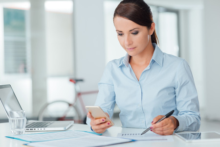 working desk: Confident businesswoman working at office desk and using a touch screen smart phone, room interior on background