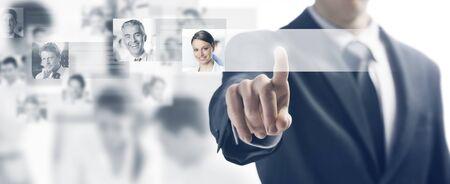Homme d'affaires utilisant une interface à écran tactile et en poussant un bouton, les gens avatars et de l'équipe d'affaires sur fond