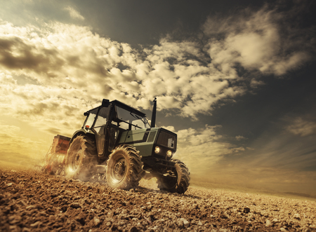 fertile: Farmer in the fields driving a tractor on fertile soil during a sunny summer day