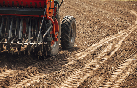 fertile: Tractor at work in the fields during a sunny summer day and tracks on the fertile soil