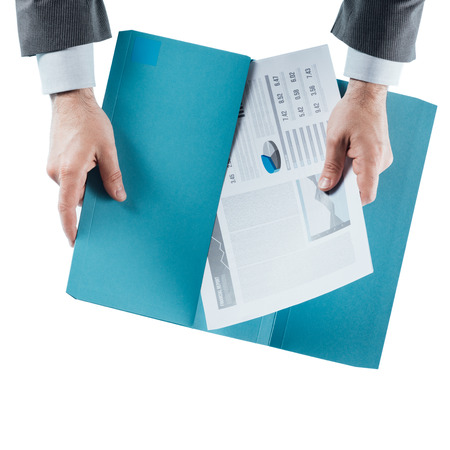 holding close: Businessman holding a financial report in a folder, hands close up, top view