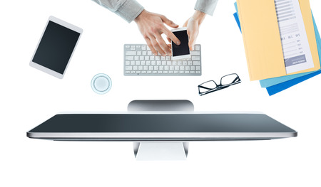 working hands: Businessman working at office desk and using an app on a touch screen smartphone, hands top view, white background
