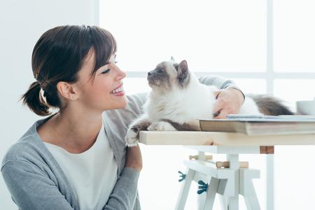 幸せな笑みを浮かべて女を自宅抱きしめると彼女の素敵な猫をつかまってテーブル、ペットおよび一体性の概念